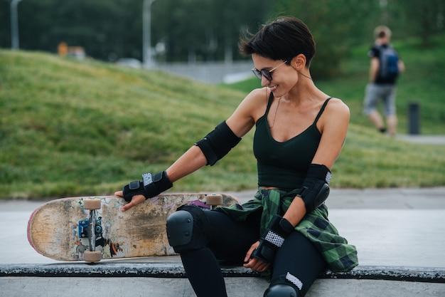 Image en contre-plongée d'une patineuse souriante aux cheveux courts reposant sur un pont, s'amusant. elle porte un équipement de protection. vue frontale. parc verdoyant en arrière-plan.