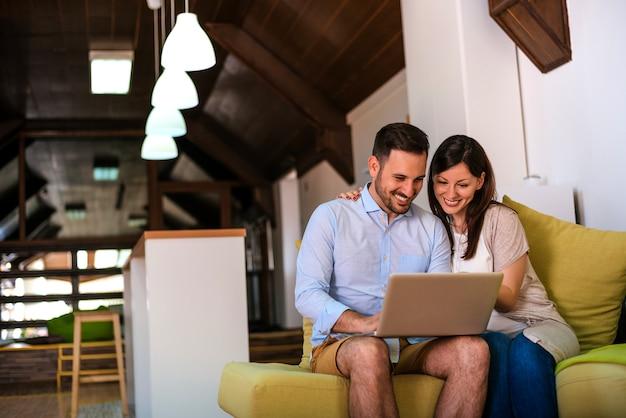 Image de copain et copine heureux assis sur un canapé tout en utilisant un ordinateur portable.