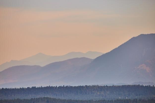 Image de couches de montagne brumeuse au coucher du soleil