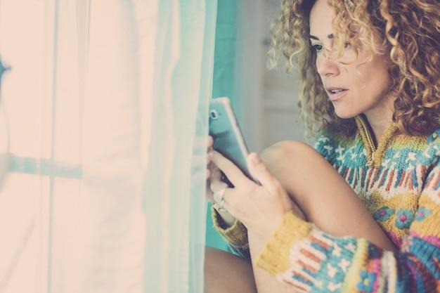 Image de couleurs de ton vintage bleu froid avec une belle jeune femme caucasienne regardant et utilisant un téléphone moderne à la maison avec une petite expression surprise