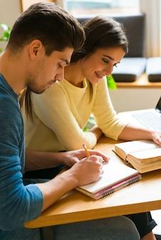 Image d'un couple d'amis jeunes étudiants dans la bibliothèque qui étudient à parler entre eux livre de lecture.