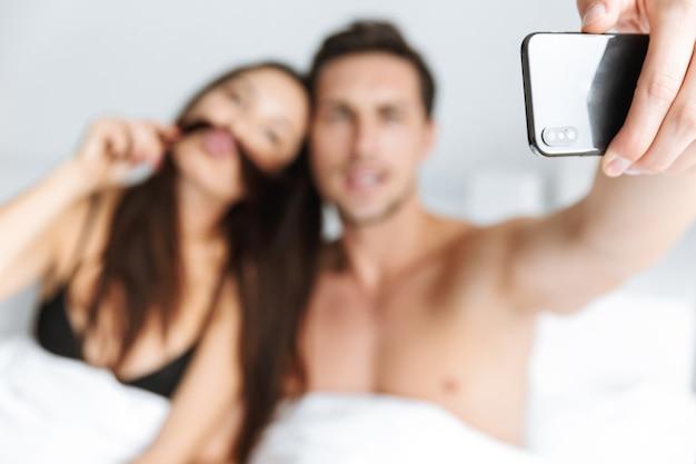 Image de couple attrayant prenant selfie sur téléphone portable, en position couchée dans son lit à la maison ou à l'hôtel