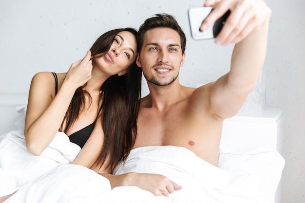 Image d'un couple européen prenant selfie sur téléphone portable, en position couchée dans son lit à la maison ou à l'hôtel