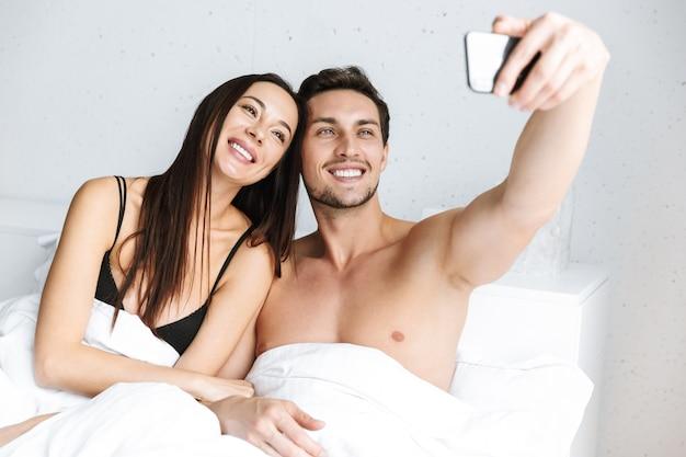 Image d'un couple romantique prenant selfie sur téléphone portable, allongé dans son lit à la maison ou à l'hôtel