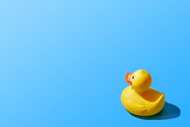 Image créative d'un canard en caoutchouc jaune isolé sur fond bleu. copiez l'espace. photo de haute qualité