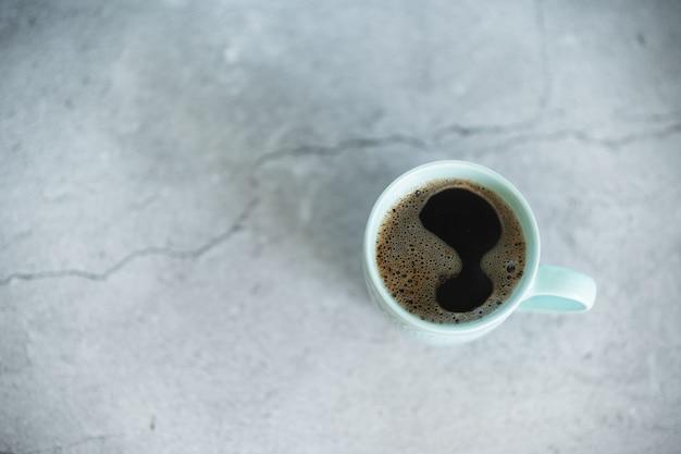 Image créative de chocolat chaud avec un bâton de crème et de cannelle dans une tasse en céramique rustique bleue.