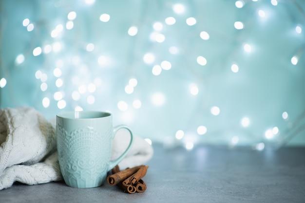 Image créative de chocolat chaud avec un bâton de crème et de cannelle dans une tasse en céramique rustique bleue