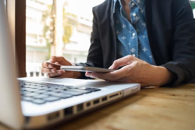 Image découpée de la femme fournissant des informations sur la carte et la clé du téléphone ou de l'ordinateur portable tout en achetant en ligne.