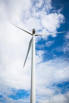 L'image derrière l'éolienne pour l'électricité par temps nuageux dans le ciel bleu.