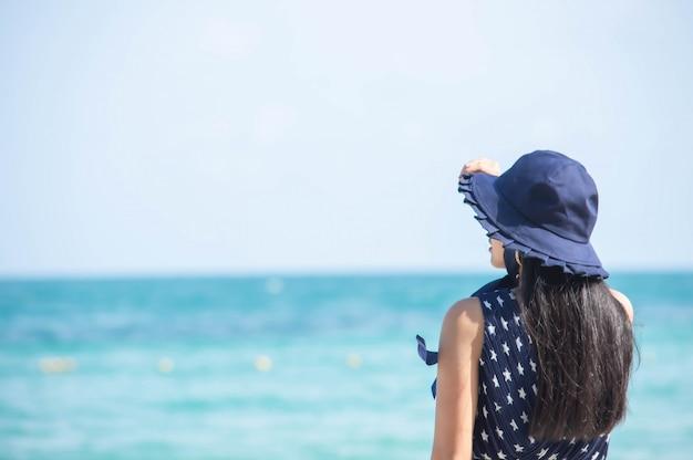 L'image derrière les femmes asiatiques porte un chapeau sur la plage de la mer de fond.