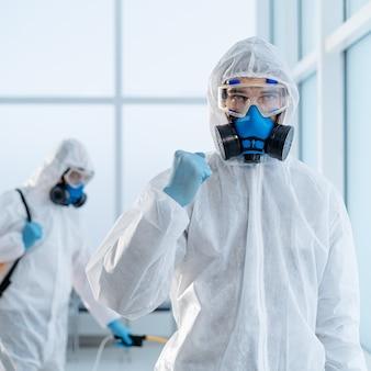 Image d'un désinfecteur confiant debout dans le hall d'un bureau