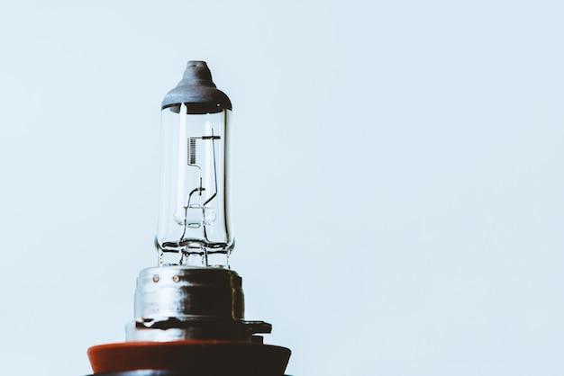 Image de détail d'ampoule de faisceau de croisement avec gros plan de filament sur fond bleu avec espace de copie.