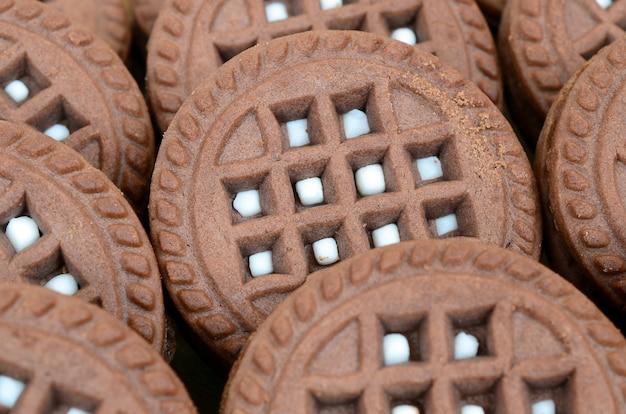 Image détaillée de biscuits sandwich rond brun foncé avec de la noix de coco remplissant de près