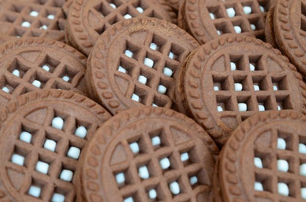 Image détaillée de biscuits sandwich ronds, brun foncé, fourrés à la noix de coco en gros plan. image de fond de plusieurs friandises pour le thé