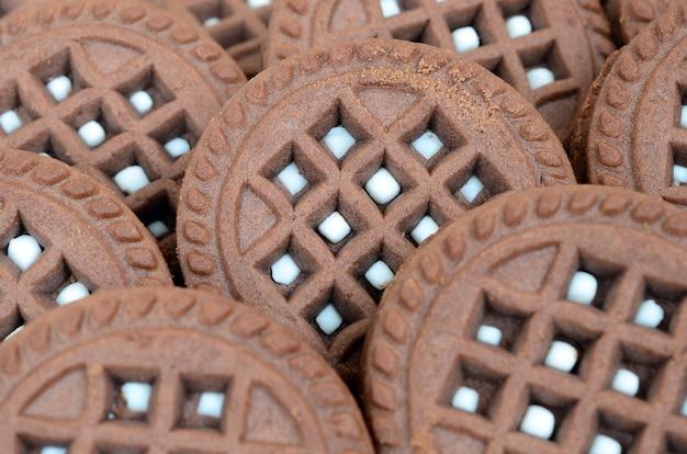Image détaillée de biscuits sandwich ronds, brun foncé, fourrés à la noix de coco en gros plan.
