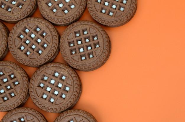 Image détaillée de biscuits sandwich ronds, brun foncé, fourrés à la noix de coco sur une surface orange. image de fond d'un gros plan de plusieurs friandises pour le thé