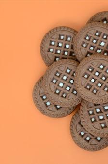 Image détaillée de biscuits sandwich ronds, brun foncé, fourrés à la noix de coco sur une surface orange.