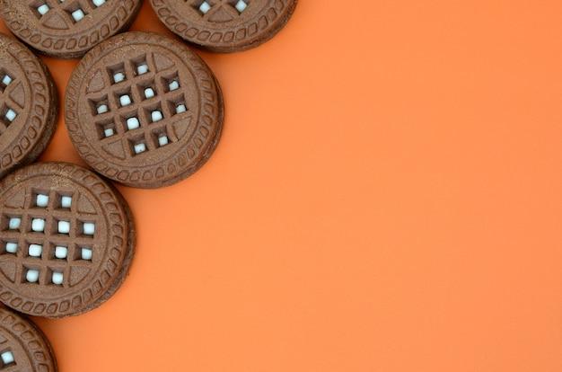 Image détaillée de biscuits sandwich ronds, brun foncé, fourrés à la noix de coco sur une surface orange