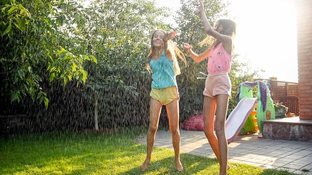 Image de deux adolescentes riantes heureuses sautant et dansant sous une pluie chaude d'été dans le jardin de la maison. famille jouant et s'amusant à l'extérieur en été