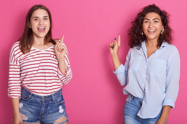 Image de deux femmes qui rient heureux avec la bouche ouverte pointant vers le haut avec les index au mur rose, des dames habillées de chemises décontractées