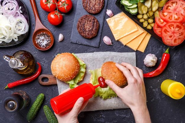 L'image sur deux hamburgers et des mains humaines ajoute le ketchup dans le hamburger