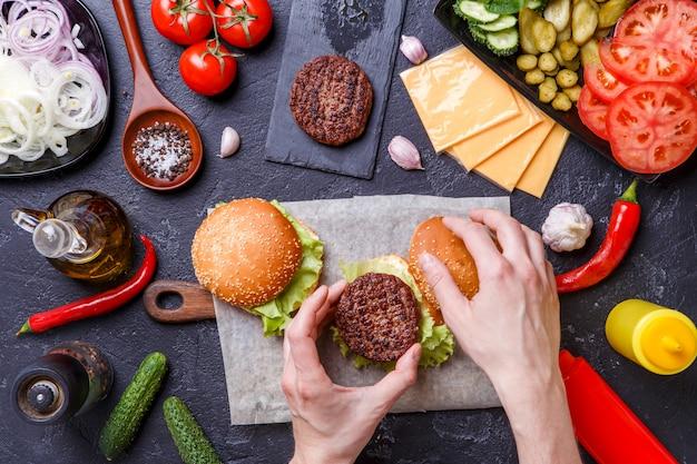 Image sur deux hamburgers, des mains humaines et des ingrédients