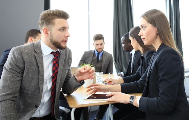 Image de deux jeunes gens d'affaires interagissant lors d'une réunion au bureau
