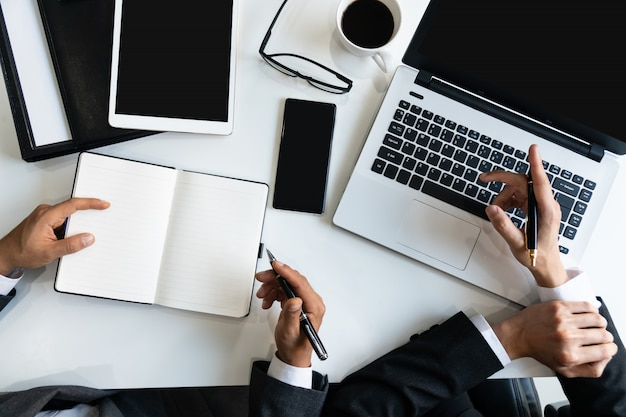 Image de deux jeunes hommes d'affaires à l'aide d'un ordinateur portable lors d'une réunion dans le bureau, les affaires et le concept de bureau