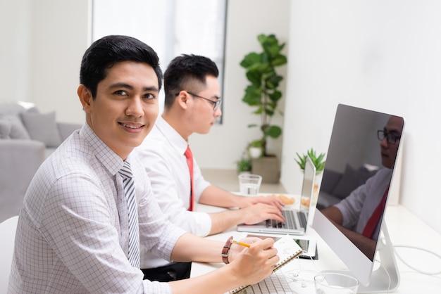 Image de deux jeunes hommes d'affaires interagissant lors d'une réunion au bureau