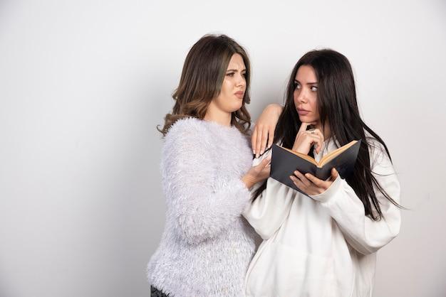 Image de deux meilleurs amis debout ensemble et posant avec un livre sur un mur blanc.