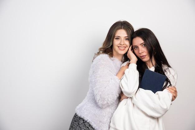 Image de deux meilleurs amis debout ensemble et posant sur un mur blanc.