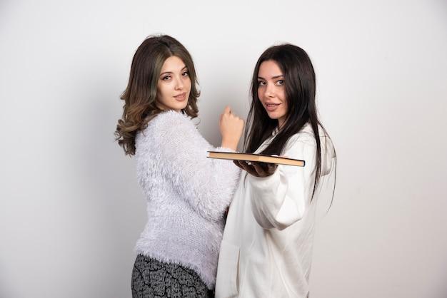 Image de deux meilleurs amis debout ensemble et regardant la caméra sur un mur blanc.