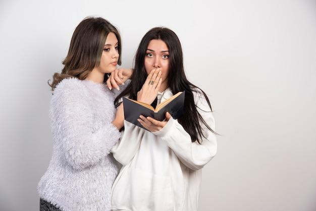 Image de deux meilleurs amis debout ensemble et regardant un livre sur un mur blanc.