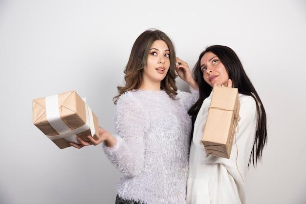 Image de deux meilleurs amis debout ensemble et tenant des coffrets cadeaux sur un mur blanc.