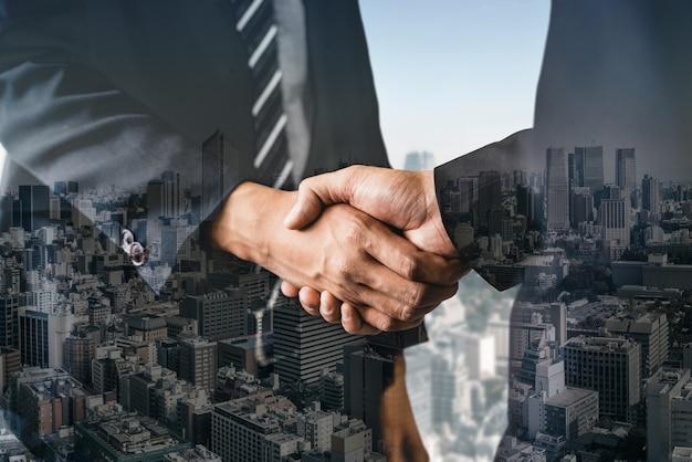 Image de double exposition de gens d'affaires poignée de main sur l'immeuble de bureaux de la ville en montrant le partenariat