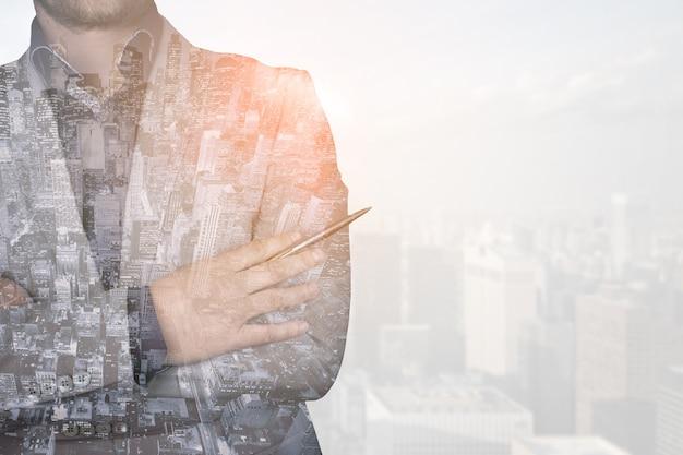 Image double exposition d'un homme d'affaires sur fond de ville moderne. le concept de l'avenir des technologies de l'entreprise et de la communication. photo de haute qualité