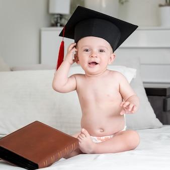 Image drôle de bébé nu en couches et chapeau de graduation assis sur un canapé