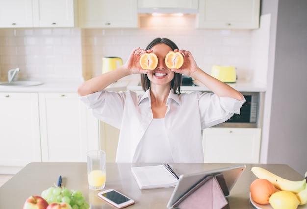 Image drôle de brune assise à table et tenant des morceaux d'orange devant les yeux. elle sourit. il y a un verre de jus, un ordinateur portable, un téléphone, une tablette et des assiettes avec des fruits sur la table.