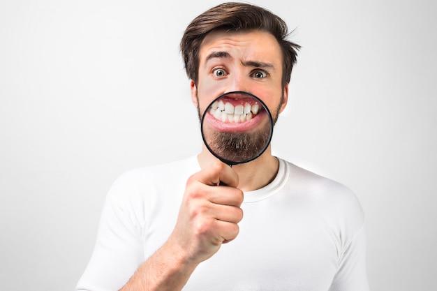Image drôle de gars tenant une loupe devant sa bouche et montrant son sourire. il se tient près d'un grand mur blanc et s'amuse. isolé sur mur blanc.