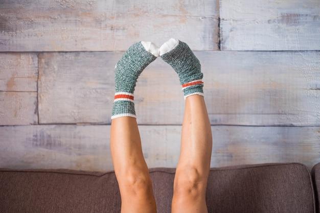 Image drôle pour les pieds avec des chaussettes agréables et drôles colorées. femme cacuasienne de haut en bas sur le canapé. cener une partie de la scène corporelle à la maison. comme la surface du bois
