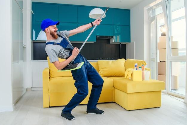 Image drôle de travailleur de nettoyage masculin dans des vêtements spéciaux jouant avec une vadrouille comme une guitare dans la cuisine