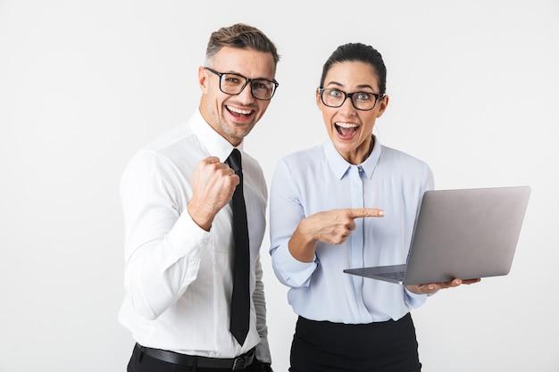Image du couple de jeunes collègues de travail isolé sur un mur blanc à l'aide d'un ordinateur portable faire le geste gagnant.