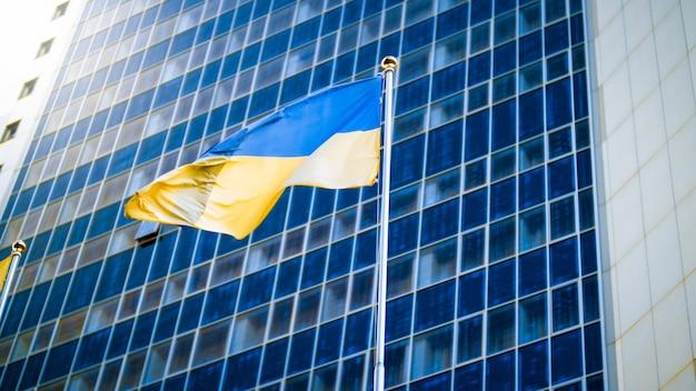 Image du drapeau national de l'ukraine contre l'immeuble de bureaux moderne. concept de l'économie, du développement et de la politique ukrainiens