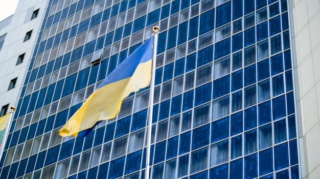Image du drapeau ukrainien jaune et bleu contre l'immeuble de bureaux d'affaires moderne
