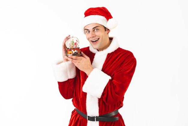 Image du jeune homme de 30 ans en costume de père noël et chapeau rouge tenant boule de noël