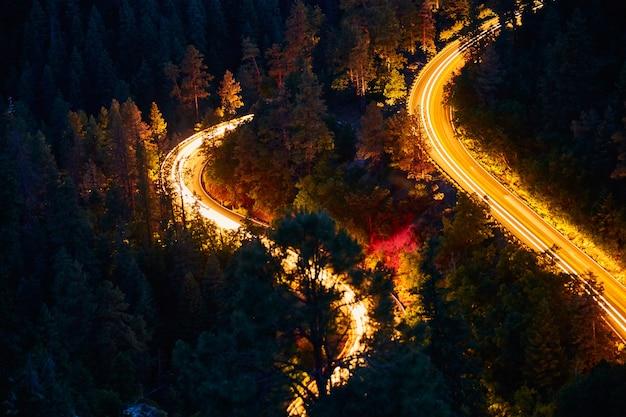 Image du paysage nocturne des routes de montagne et du flou de la conduite des voitures
