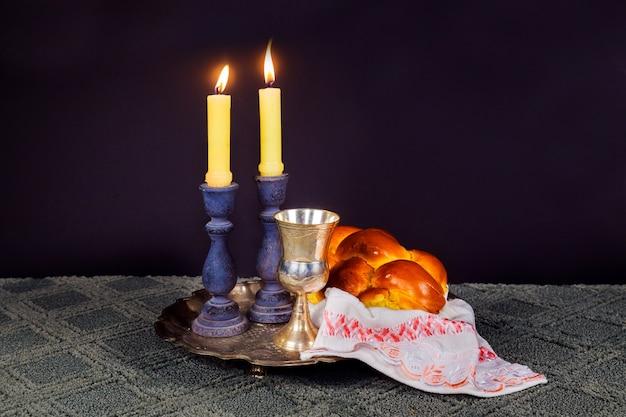 Image du sabbat. pain challah et candelas sur table en bois samedi sabbat