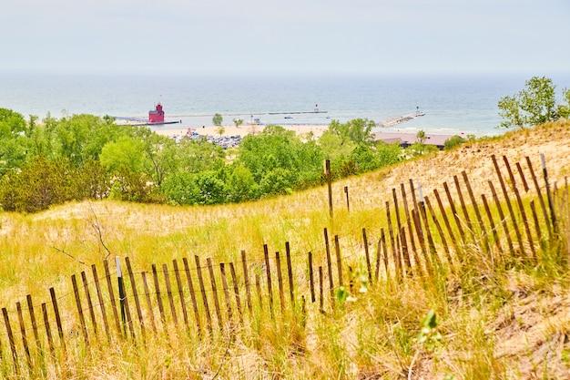 Image de dunes de sable au michigan avec vue sur le phare rouge et le grand lac à distance