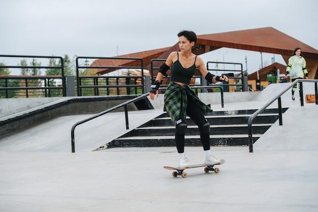 Image dynamique d'une patineuse confiante aux cheveux courts à cheval sur sa planche sur un pavage en béton au skatepark. elle porte un équipement de protection.