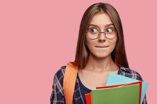 Image d'une écolière réfléchie intriguée, presse les lèvres, regarde mystérieusement de côté, pense à quelque chose